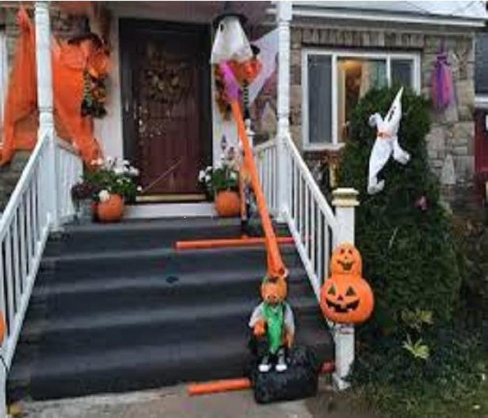 Stairs decorated for Halloween with PVC chute running down handrail