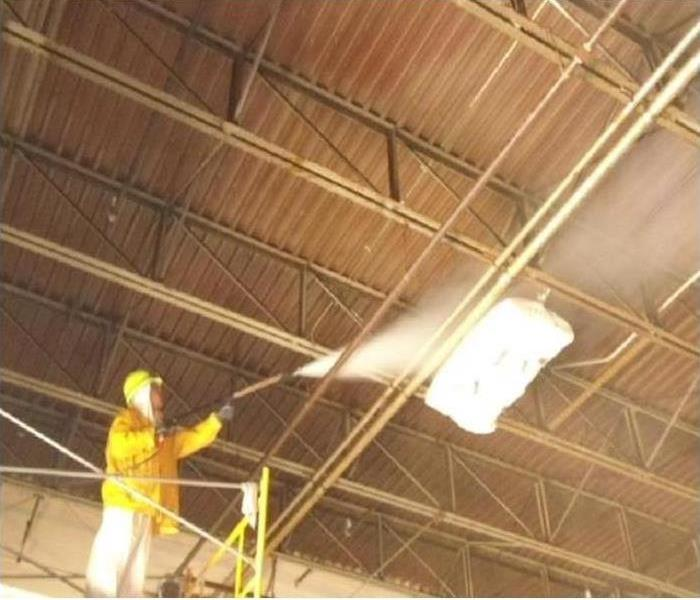 Technician on scissor lift pressure washing wood beams